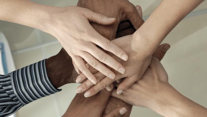 Trzymające się dłonie osób różnych narodowości