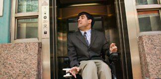 Mężczyzna na wózku inwalidzkim opuszczający windę