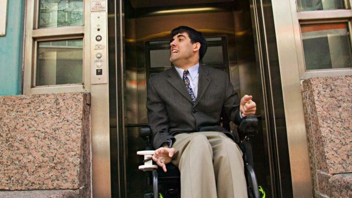 Mężczyzna na elektrycznym wózku inwalidzkim opuszczający windę
