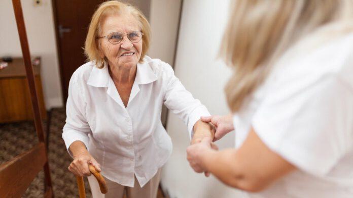 Asystentka pomagająca starszej kobiecie wejść po schodach