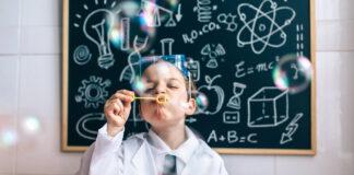 Chłopczyk dmuchający bańki mydlane przed tablicą szkolną