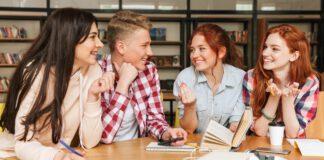 Grupa czworga młodych ludzi dyskutujących przy stole
