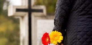 Mężczyzna z kwiatami na cmentarzu